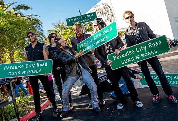 """Guns N' Roses band members pose with """"Paradise City Road"""" sign at The Joint"""