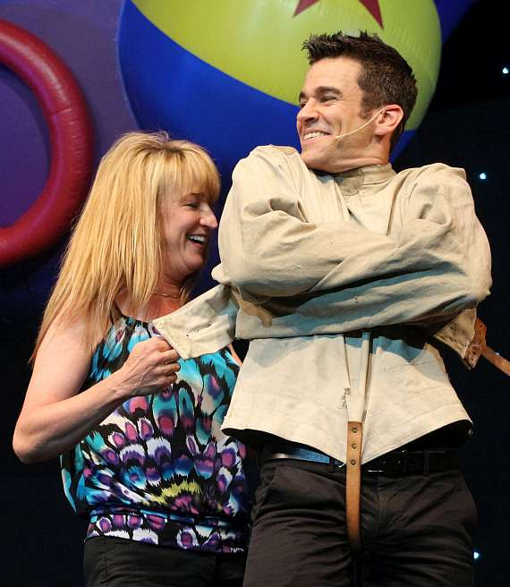 An audience member straps Jeff Civillico into a straightjacket