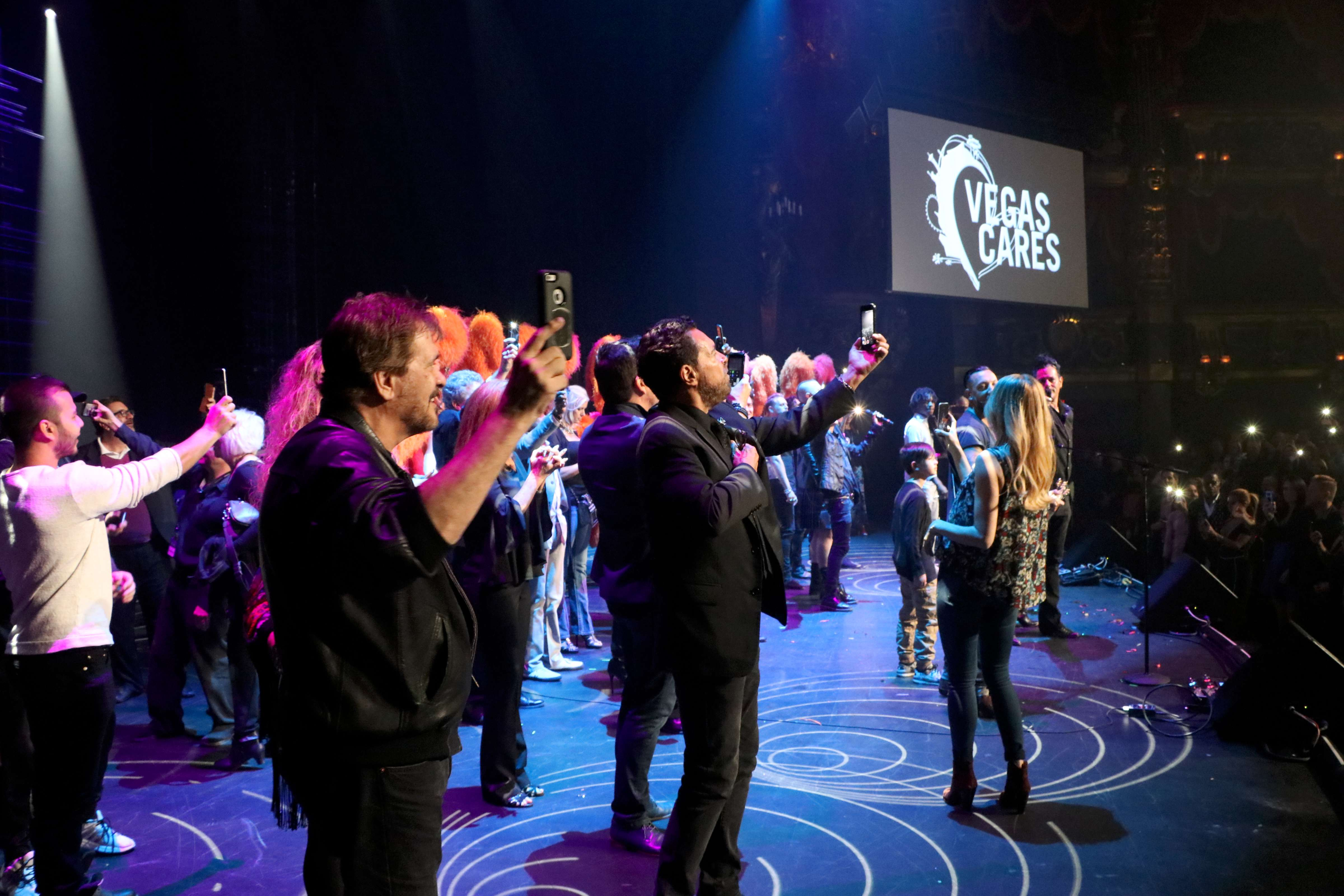"""Cast of """"Vegas Cares"""" joins the band on stage"""