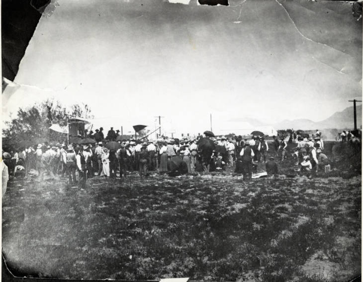Black and white image of a large group of people bidding for lots of land during Clark's Las Vegas Townsite auction.