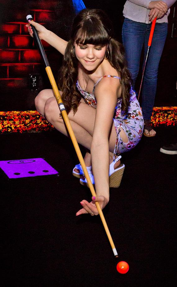 Claire Sinclair tries playing golf with a pool cue at KISS Monster Mini Golf in Las Vegas