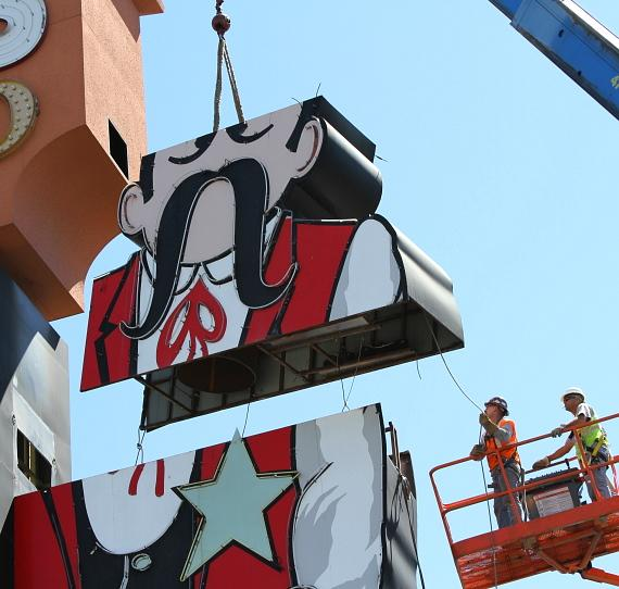 Workers from Federal Heath Sign Company begin removing the iconic Terrible's Cowboy neon sign as the property begins the transition to its new name, Silver Sevens Hotel & Casino