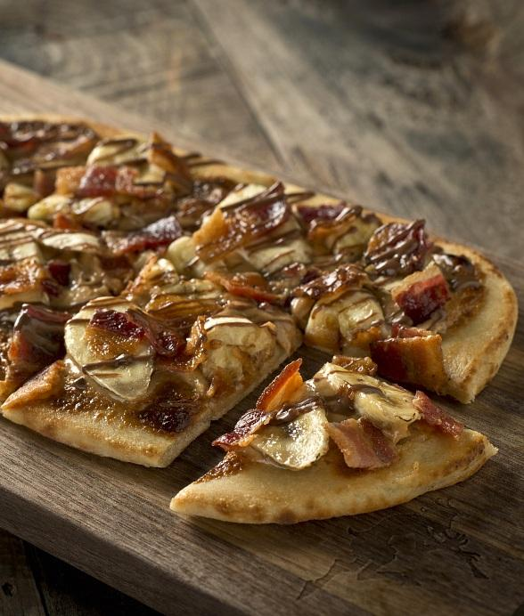 The Fat Elvis, a twist on Elvis' favorite sandwich, is an indulgent flatbread topped with peanut butter, bacon bits and banana slices drizzled with Nutella.