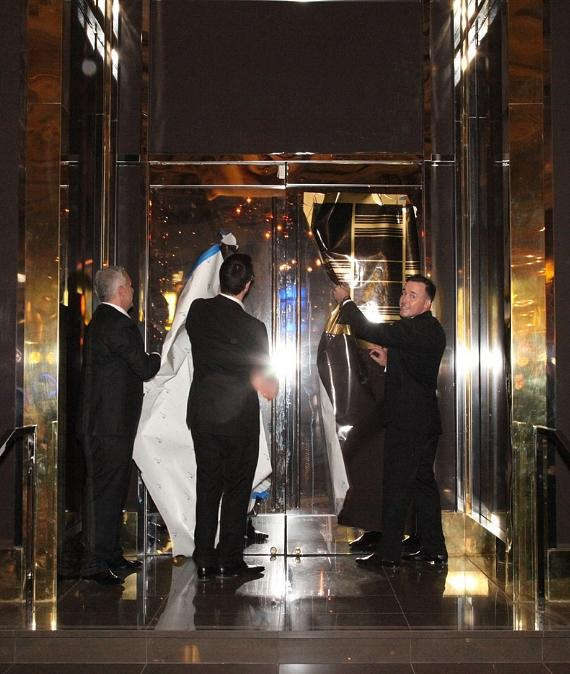 Michael Greco, Steve Kennedy and David Furnish remove the final construction wrap from the FIZZ Las Vegas entrance.