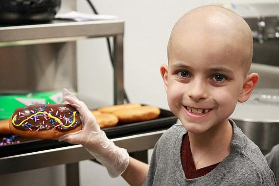 Gavin Prince poses with a Krispy Kreme  donut made with his winning recipe