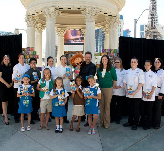Robyn Ratcliffe Manzini, President of the Board of Directors for Girl Scouts of Southern Nevada; Chef Marisela Espinosa, Caesars Palace; Chef Brittany Givero, Three Square; Chef Marie Yonge, Giada; Chef Kimberly Vitou, MGM Grand; Celebrity Impressionist Terry Fator and Emma the Puppet; Liz Ortenburger, CEO Girl Scouts of Southern Nevada; Chef Cynthia Werth, Stratosphere; Chef Tamira White, Hard Rock Hotel & Casino; Chef Vivian Chang, Downtown Grand; Chef Jeanette Droegmoeller, Bellagio. Front: Five Girl Scouts in Daisy, Brownie and Junior uniforms.