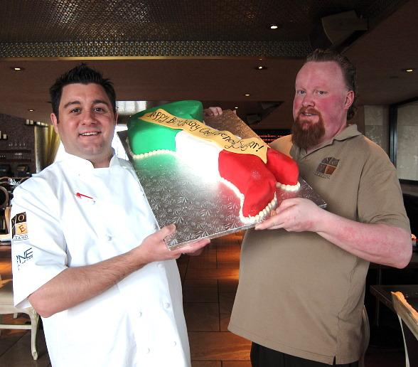 """Executive Chef Geno Bernardo of Nove Italiano and Mixologist Jack """"Sugar"""" O'Brien receive a birthday cake in the shape of Italy at the April 9 cooking class"""
