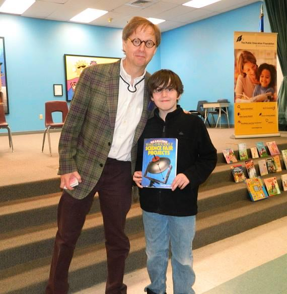 """Harrah's Las Vegas Comedy-Magician Mac King poses with 5th grader Josh Tribble during an assembly to celebrate Nevada Reading Week at Edith Garehime Elementary School. Tribble helped the magician perform his """"Cloak of Invisibility"""" trick during the assembly."""