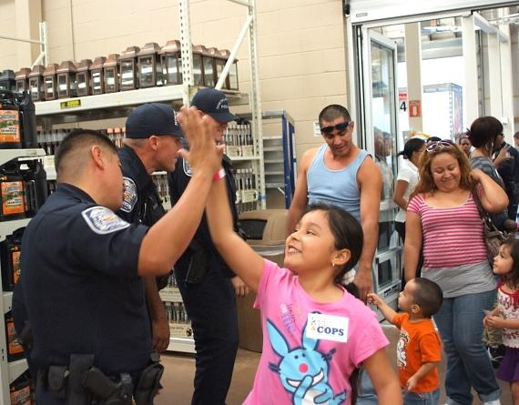 NLVPD officer gives a student a high-five at United Way's Kids & Cops event at Walmart