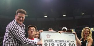 Guns and Ammo Garage Co-Owner Mark Cole presents a check to members of Special Olympics Nevada and Regional Vice President Maggie Schwarz at the 2013 PBR World Finals