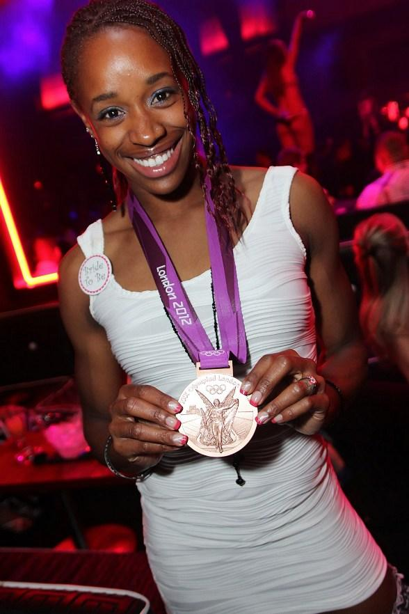 Olympian Janay DeLoach with her gold medal at Rain Nightclub