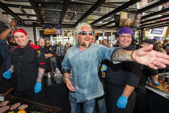 Guy Fieri cooks up his award-winning Bacon Mac-N-Cheese Burgers on the newly redesigned patio to celebrate the one year anniversary of Guy Fieri's Vegas Kitchen & Bar at The LINQ Hotel & Casino