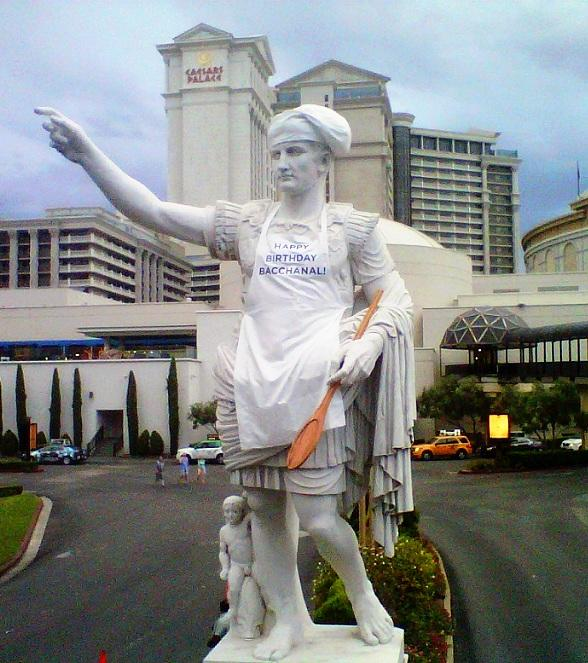 """The iconic Caesar Augustus leads the celebration of Bacchanal's birthday with a chef's hat, """"happy birthday Bacchanal"""" apron and chef's spoon"""
