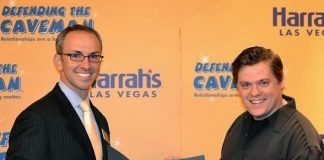 """Christian Stuart, Harrah's regional vice president and assistant general manager presents Chris Allen, new leading caveman of """"Defending The Caveman,"""" with a proclamation from Las Vegas Mayor Carolyn G. Goodman naming June 24, 2013 """"'Defending the Caveman' – Chris Allen Day"""" in Las Vegas in honor of the show's sixth anniversary in Las Vegas"""