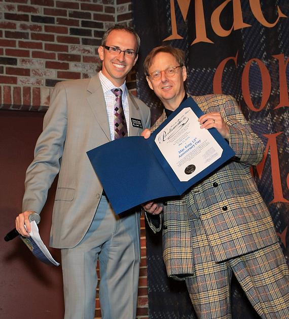 """Christian Stuart, Harrah's regional vice president and assistant general manager presents Comedy-Magician Mac King with a proclamation from Mayor Carolyn G. Goodman naming May 11, 2013 """"Mac King 13th Anniversary Day"""" in Las Vegas."""