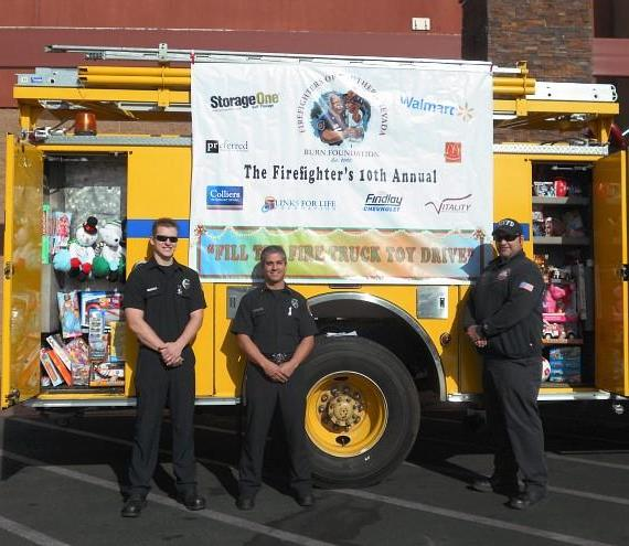 """Firefighter Ben Bodine hands out a toy fire truck to Kyirean Reed during a visit to Marion Cahlan Edison Elementary School where firefighters delivered toys to the students as part of Firefighters of Southern Nevada's 10th Annual """"Fill the Fire Truck Toy Drive."""""""