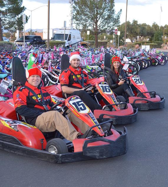 """Pole Position Raceway """"elves"""" pose inside the high performance electric go karts at NV Energy as they deliver 1,000 race passes during the 17th Annual 98.5 KLUC Toy Drive"""