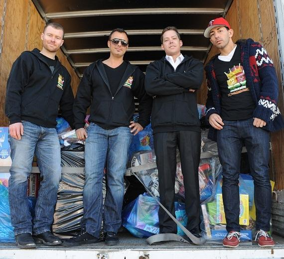 XS and Tryst executive team poses in front of one of four semi trucks full of toys. From left to right: Executive Director of VIP Services John Wood, General Manager Yannick Mugnier, Co-Owner and Managing Partner Jesse Waits, Director of Strategic Marketing Ronn Nicolli