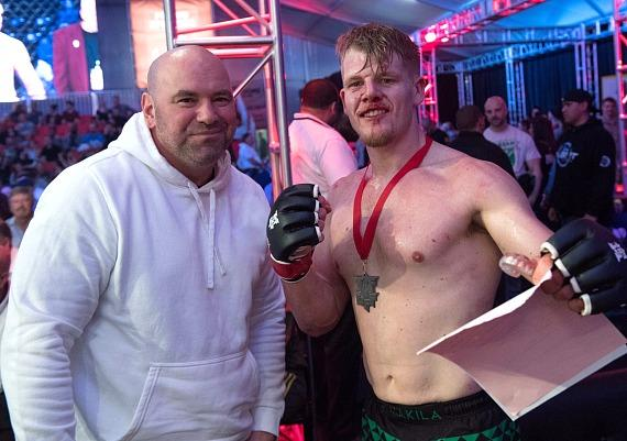 Dana White poses with MMA Fighter cage side after his match