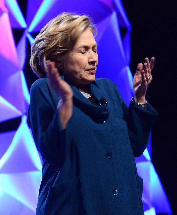 Former U.S. Secretary of State Hillary Rodham Clinton dodges a shoe thrown by a woman in the audince