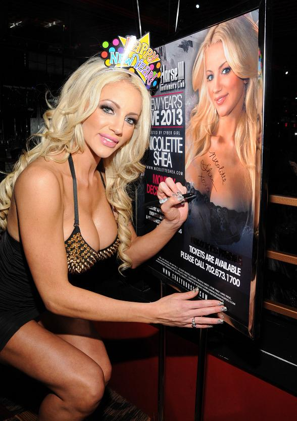 Nicolette Shea poses with event flyer at Crazy Horse III