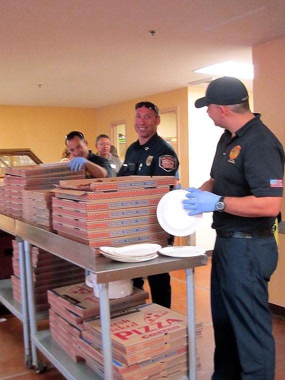Las Vegas Fire & Rescue's firefighters Ryan Cantwell and Mitch Steinbers dish up pizza to women and children at The Shade Tree